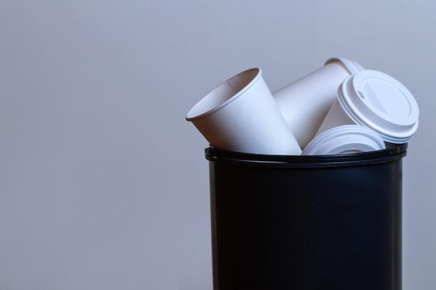 Bidone della spazzatura traboccante di carta, tazze di caffè. dipendenza da caffè e bere molto sfondo di tazze di caffè