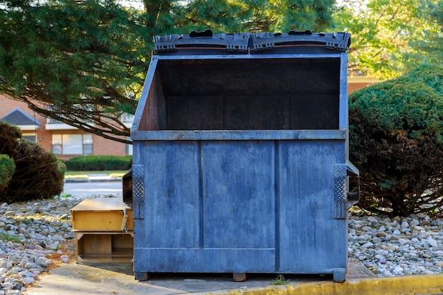 Contenitori della spazzatura di lattine vicino a edifici residenziali in ecologia, inquinamento ambientale.