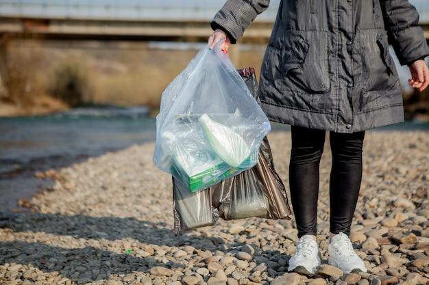 Immondizia nella natura, pulendo l'ambiente in primavera sul fiume dalla spazzatura una donna in guanti blu di lattice usa e getta in un grande sacchetto di plastica blu.