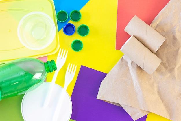 Immondizia, plastica e carta, su uno sfondo colorato astratto. ecologia e inquinamento del pianeta terra. ordinamento dei rifiuti.