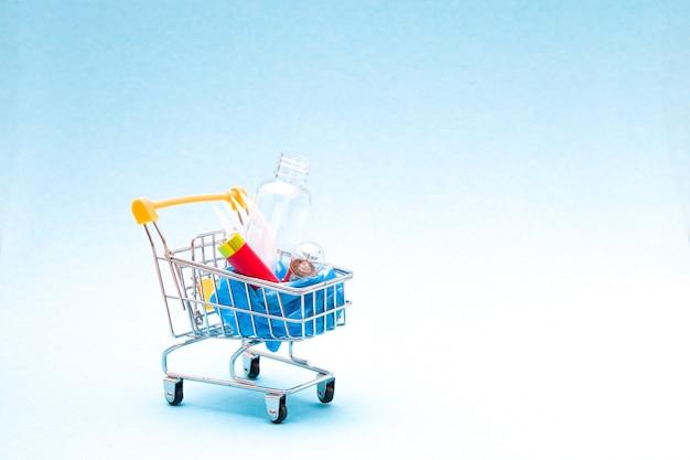 Immondizia per il riciclaggio in un mini carrello su uno sfondo blu copia spazio, zero rifiuti concetto di stile di vita