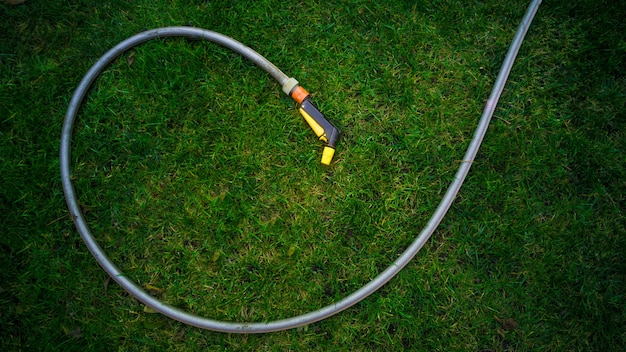 Tubo da giardino sdraiato sull'erba verde fresca in giardino