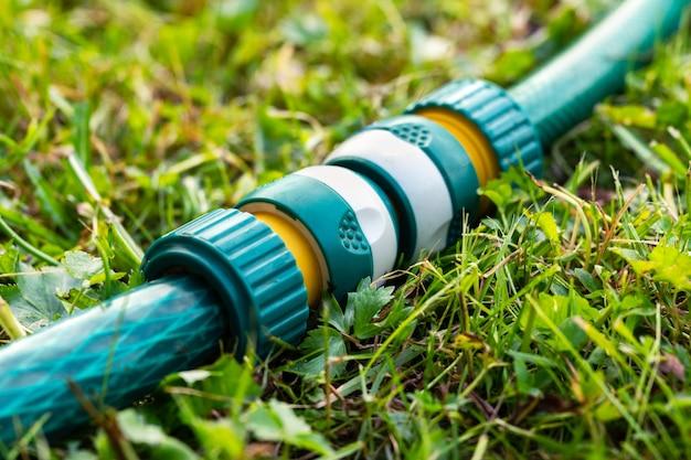 Tubi per irrigazione da giardino collegati con un moderno connettore per tubo di plastica sdraiato sull'erba