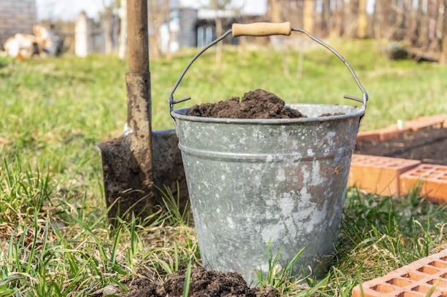 Attrezzi da giardino, un secchio di terra e una pala. lavori stagionali nel giardino del cottage.