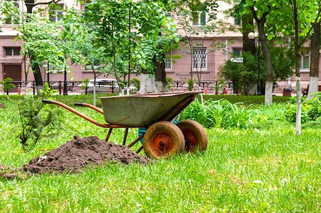 Carriola da giardino per il trasporto del terreno nell'area suburbana. vista in giardino sull'erba.