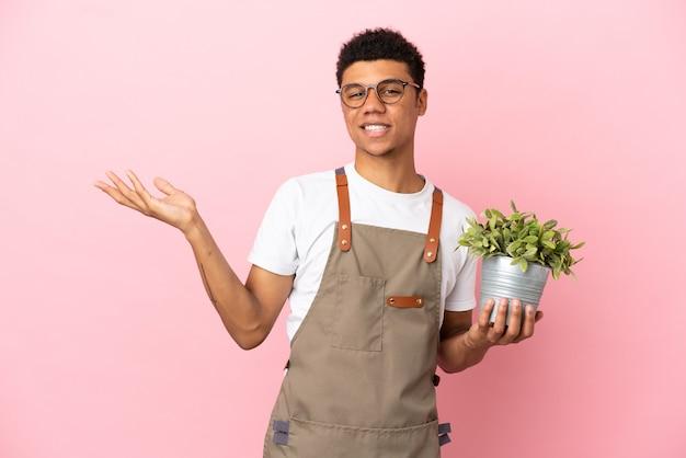 Giardiniere africano che tiene una pianta isolata su sfondo rosa che allunga le mani di lato per invitare a venire