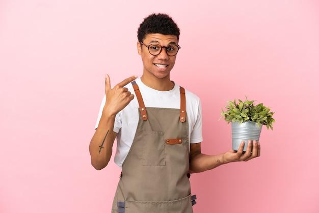 Giardiniere africano che tiene una pianta isolata su sfondo rosa che fa un gesto di pollice in alto