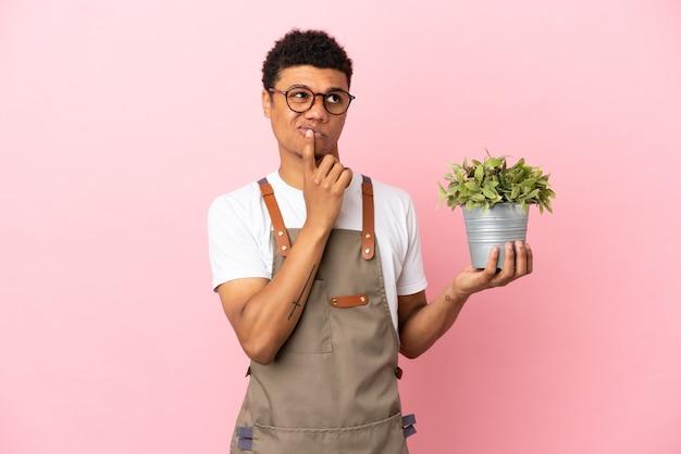 Giardiniere africano che tiene una pianta isolata su sfondo rosa avendo dubbi mentre guarda in alto