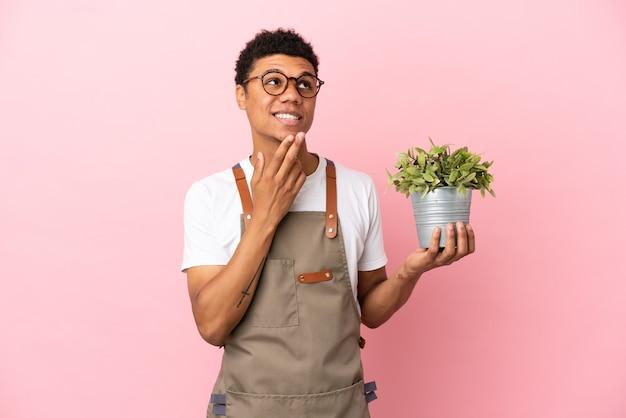 Giardiniere uomo africano che tiene una pianta isolata su sfondo rosa guardando in alto mentre sorride
