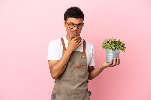 Giardiniere africano che tiene una pianta isolata su sfondo rosa pensando