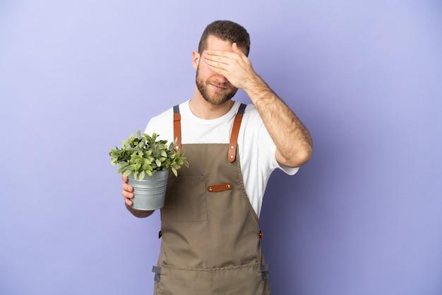 Uomo caucasico del giardiniere che tiene una pianta isolata su fondo giallo che copre gli occhi con le mani. non voglio vedere qualcosa