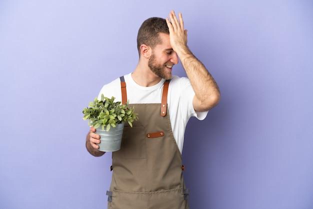 Uomo caucasico del giardiniere che tiene una pianta isolata