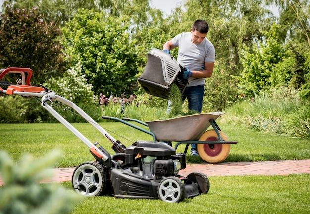 Giardiniere che svuota l'erba della falciatrice da giardino in una carriola dopo la falciatura.