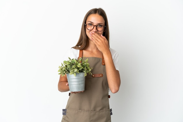 Ragazza del giardiniere che tiene una pianta sopra fondo bianco isolato felice e sorridente che copre la bocca con la mano
