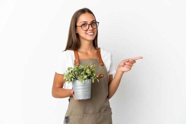 Ragazza del giardiniere che tiene una pianta sopra fondo bianco isolato che indica dito al lato