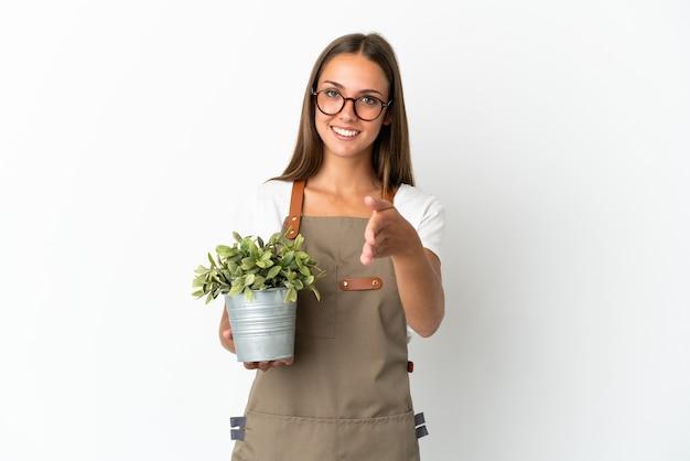 Ragazza del giardiniere che tiene una pianta sopra fondo bianco isolato che agita le mani per chiudere un buon affare