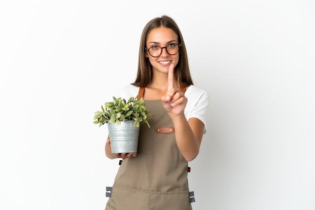 Ragazza del giardiniere che tiene una pianta sopra fondo bianco isolato che mostra e che alza un dito