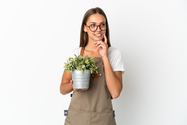 Ragazza giardiniere che tiene una pianta su sfondo bianco isolato pensando a un'idea mentre guarda in alto