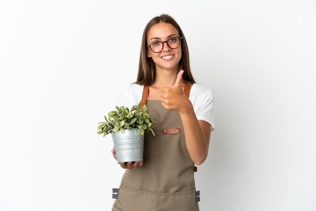 Ragazza giardiniere che tiene una pianta su sfondo bianco isolato con il pollice in alto perché è successo qualcosa di buono