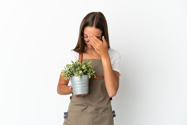 Ragazza del giardiniere che tiene una pianta sopra fondo bianco isolato con l'espressione stanca e malata