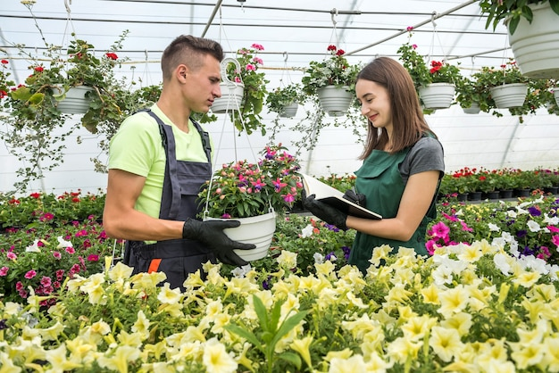 Il giardiniere e il suo manager lavorano in un moderno negozio di piante da vivaio con un blocco per appunti in una serra