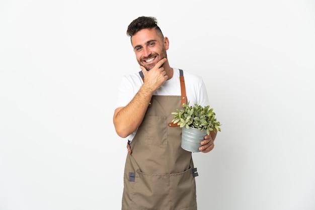 Uomo del giardiniere che tiene una pianta sopra fondo bianco isolato felice e sorridente