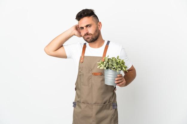 Uomo del giardiniere che tiene una pianta sopra fondo bianco isolato che ha dubbi