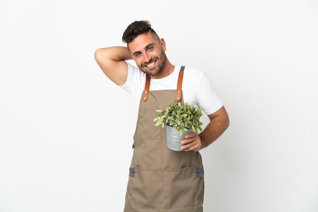 Uomo del giardiniere che tiene una pianta sopra fondo bianco isolato che ride