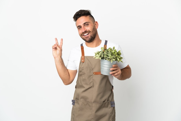 Uomo del giardiniere che tiene una pianta sopra fondo bianco isolato che sorride e che mostra il segno di vittoria