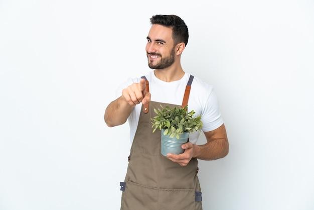 Uomo del giardiniere che tiene una pianta isolata sulla parte anteriore bianca di puntamento della parete con l'espressione felice