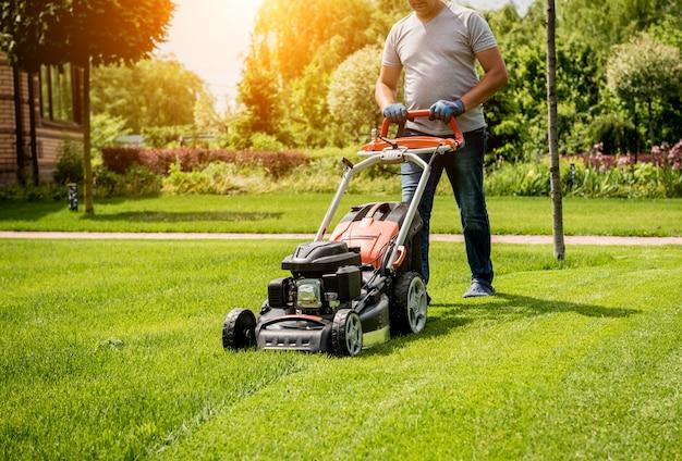 Giardiniere che falcia il prato. progettazione del paesaggio. sfondo verde