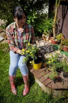 Giardiniere che pianta con gli strumenti dei vasi da fiori. mano della donna che pianta la petunia dei fiori nel giardino di estate a casa, all'aperto il concetto di giardinaggio e fiori.