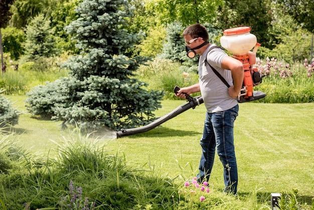 Giardiniere in maschera protettiva e bicchieri che spruzzano alberi di pesticidi tossici