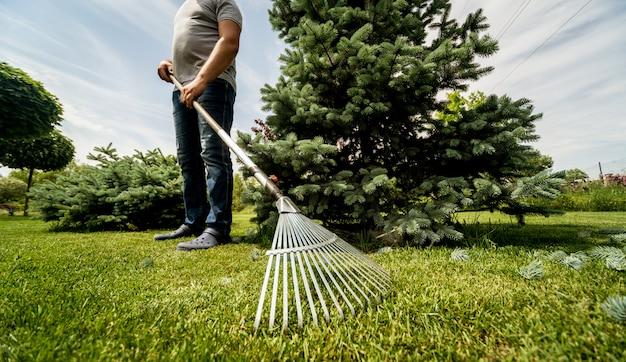 Giardiniere che rastrella le foglie di taglio nel giardino.