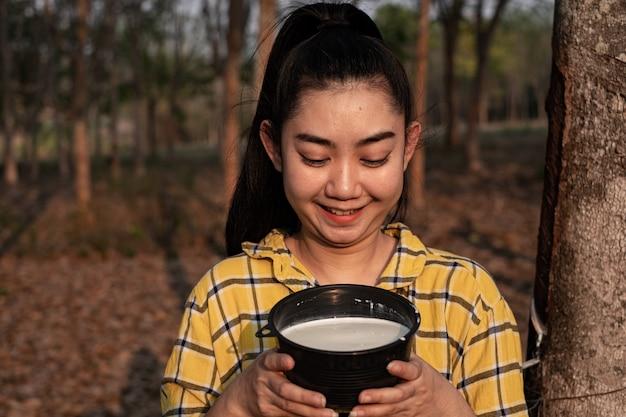 La giovane donna asiatica del giardiniere guarda una tazza piena di latte crudo di gomma para di albero