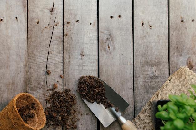 Concetto di giardinaggio. pentola eco con pianta verde, pala, sporcizia su fondo in legno. hobby da giardino.