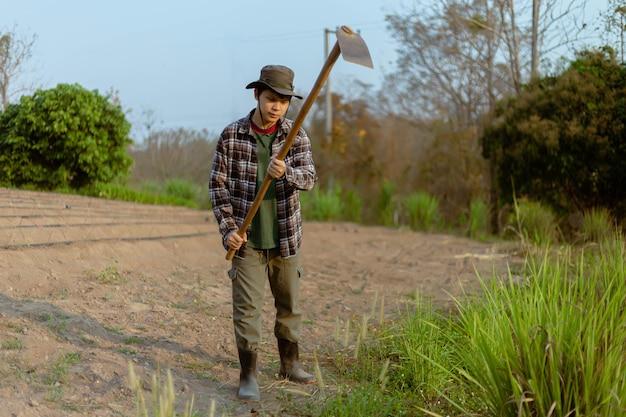 Concetto di giardinaggio un agricoltore maschio che utilizza una zappa che scava nel terreno per realizzare orti che si preparano per la coltivazione delle piante.