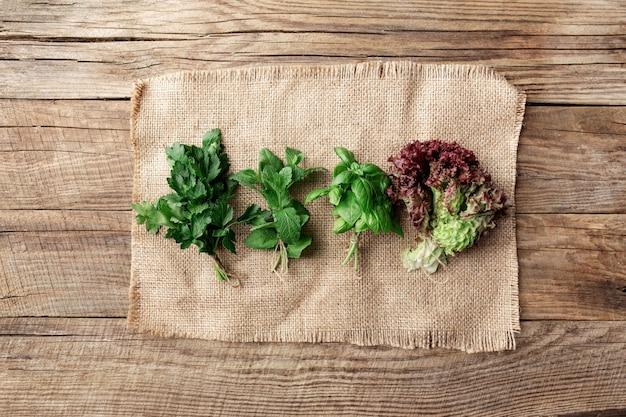 Concetto di giardinaggio e alimentazione sana con diverse erbe e foglie di insalata, basilico, menta, radicchio, prezzemolo e sedano su tela di sacco su sfondo di legno
