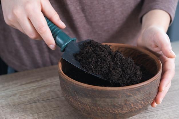 Giardinaggio a casa, mani delle donne che versano il terreno per le piante in vaso di ceramica. passo dopo passo, tutorial.