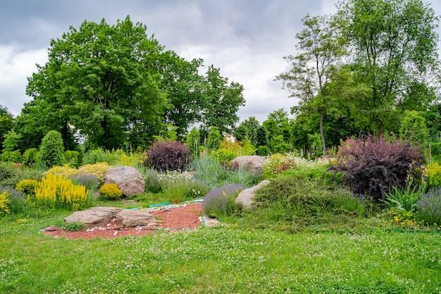 Paesaggio di giardinaggio e progettazione del paesaggio come un prato da giardino perenne con un'aiuola e piante ornamentali in un percorso paesaggistico decorativo.