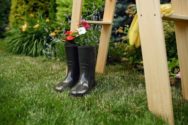 Attrezzi da giardinaggio, fiori in stivali di gomma sulle scale di legno, nessuno. attrezzatura per giardiniere o fiorista, hobby estivo, giardino