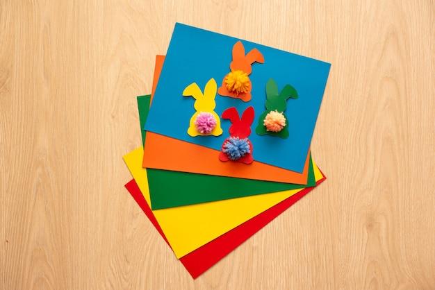 Ghirlanda di coniglietti colorati sulla tavola di legno.