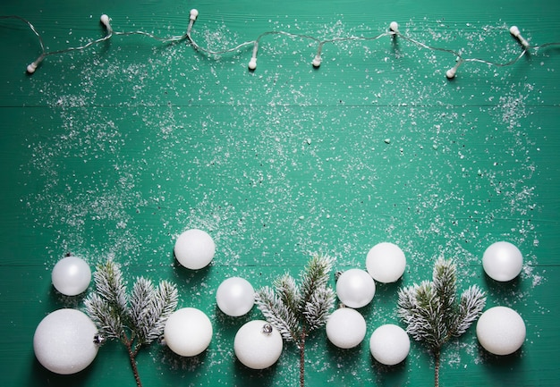 Una ghirlanda di rami di abete e palline di natale bianche si trovano su uno sfondo di legno verde