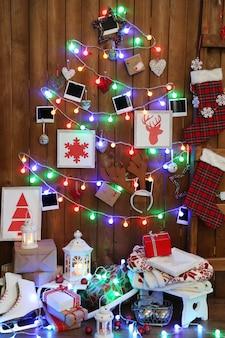 Ghirlanda a forma di albero di natale su parete in legno, scatole regalo e lanterna. concetto di atmosfera natalizia