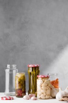 Aglio, asparagi e olive conservate in barattoli di vetro con copia spazio