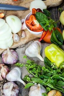 Aglio e basilico verde durante la cottura, tavolo da cucina durante la cottura degli alimenti, primi piani