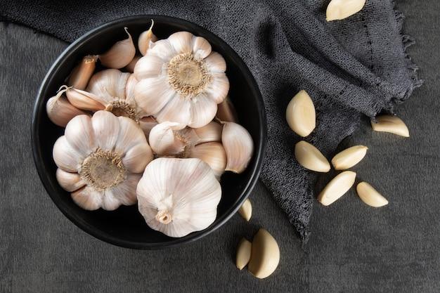 Spicchi d'aglio e lampadina in ciotola nera su tessuto e sfondo scuro.