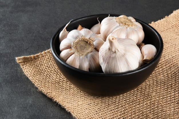 Spicchi d'aglio e lampadina in ciotola nera su iuta e sfondo scuro.