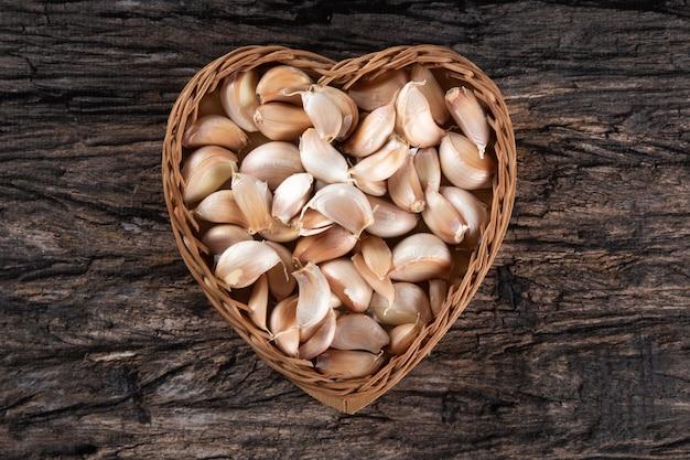 Spicchi d'aglio e bulbo nel cesto di cuore su fondo di legno rustico..