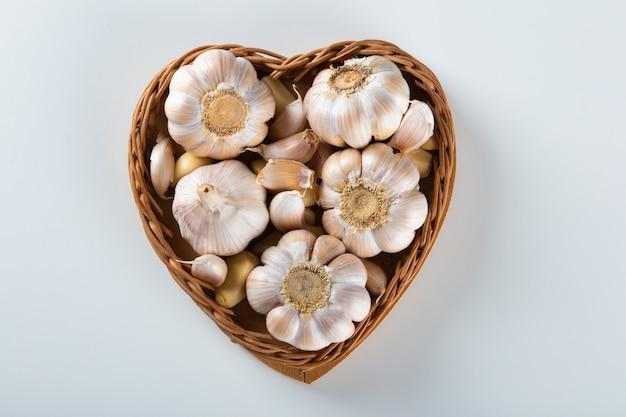 Spicchi d'aglio e lampadina nel cesto del cuore su sfondo bianco.